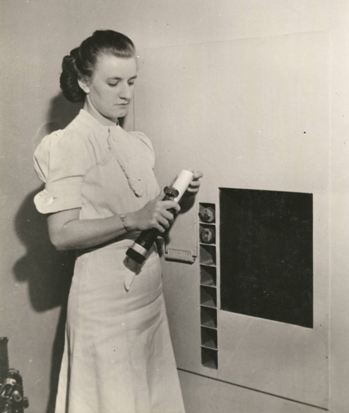 picture of a woman with a pneumatic tube in her hand taking out a pull slip