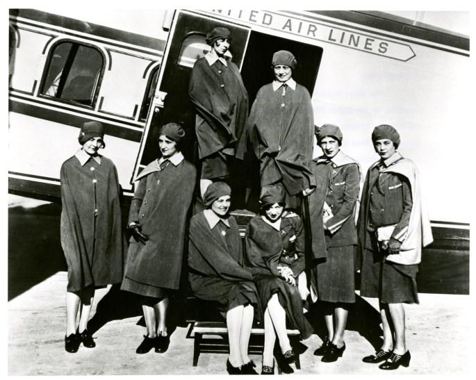 Stewardess posing outside an airplane.
