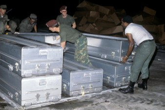 Image of US Military personnel stack transfer cases containing the remains of the victims of the Jonestown Tragedy onto a pallet for shipment to Dover Air Force Base, Delaware (NAID 6413440)