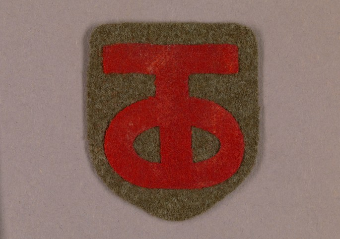 insignia of a red T intersecting a red O on a green patch