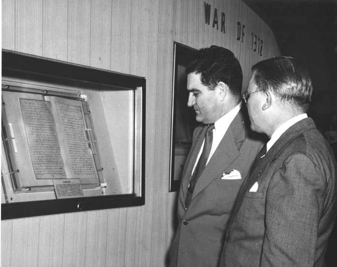 two men viewing document inside glass case.