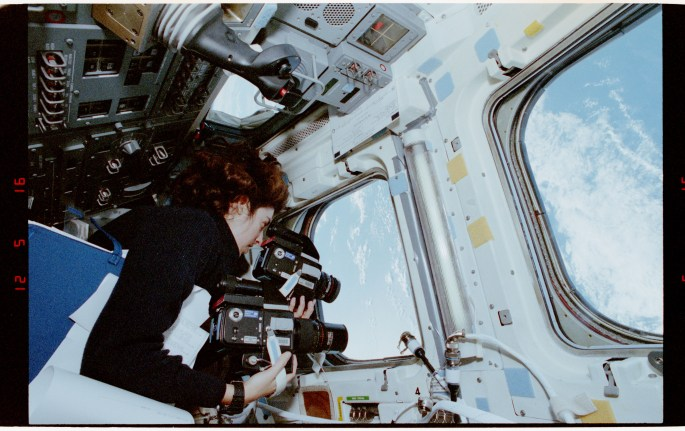 Ochoa in a space shuttle looking out a window down to Earth