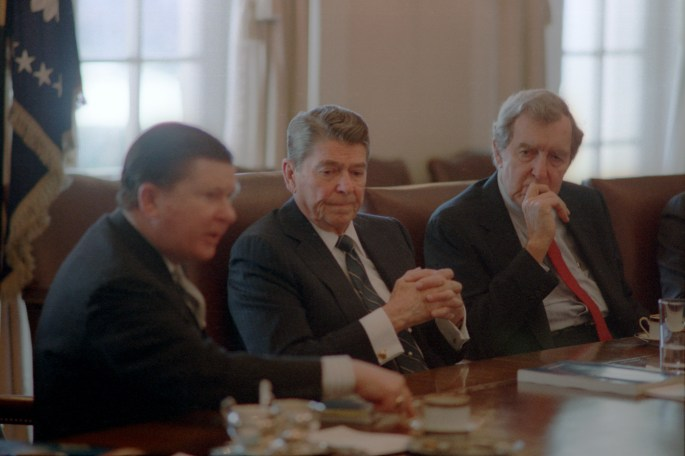 Reagan at a conference table with his hands folded, sitting inbetween 2 other men