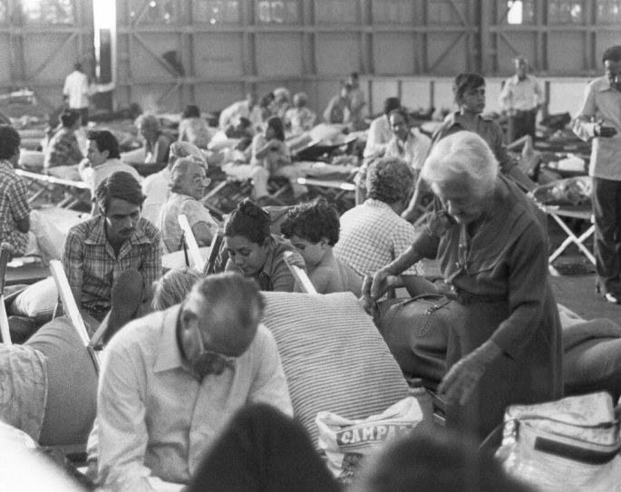 dozens of people sitting in a large hanger