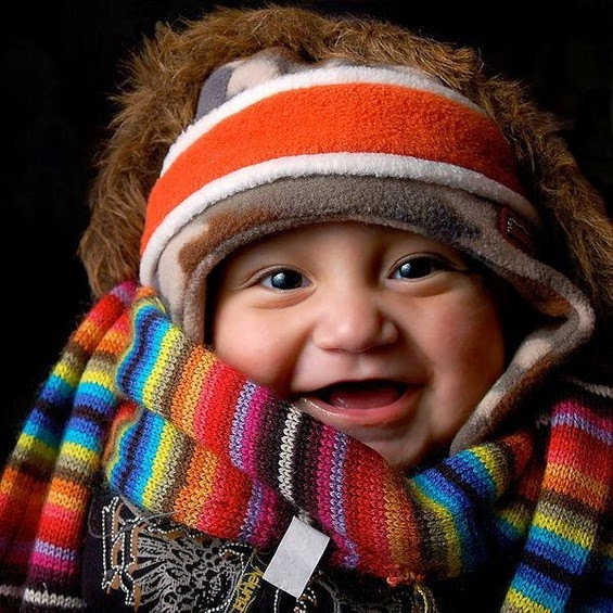 A baby wearing many items of winter clothing
