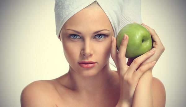 В руках зеленое яблоко