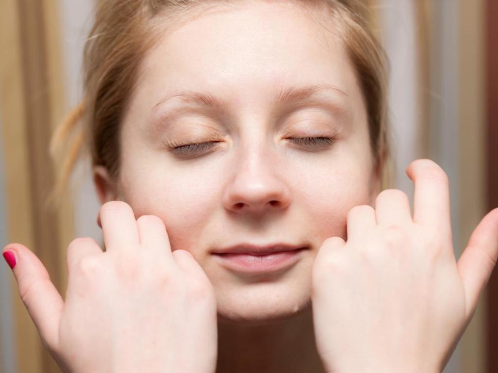 Девушка гладит свое лицо