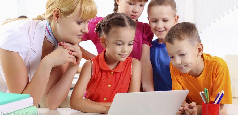 учительница с детьми смотрит на экран компьютера