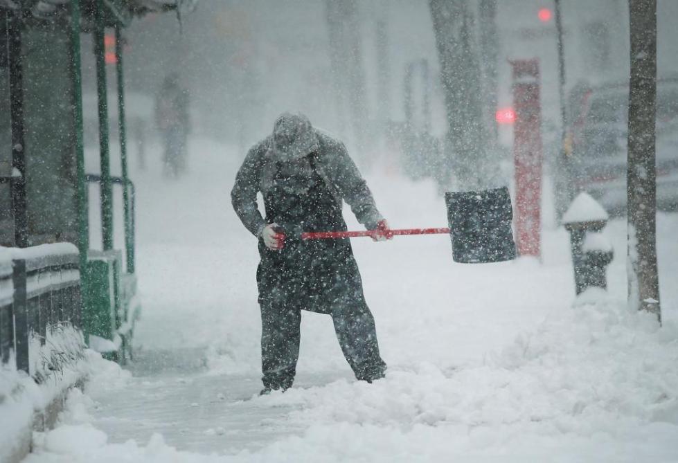 Мужчина чистит тротуар от снега