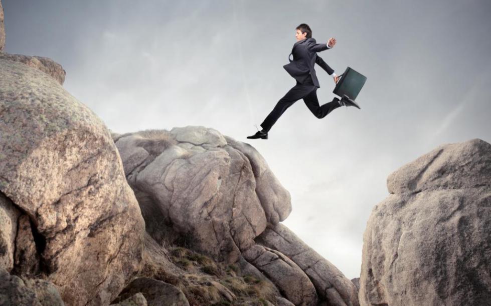 мужчина прыгает через овраг
