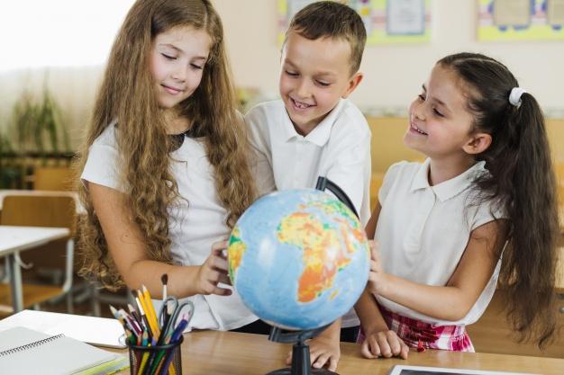 школьники рассматривают глобус