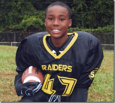Carl Joseph Walker-Hoove age 11. He is wearing a football uniform, holding a helmet and smiling.