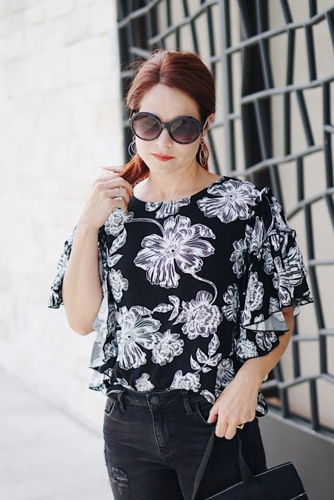 black and white floral blouse, black jeans, round sunglasses, black sunnies, red hair, casual chic inspiration