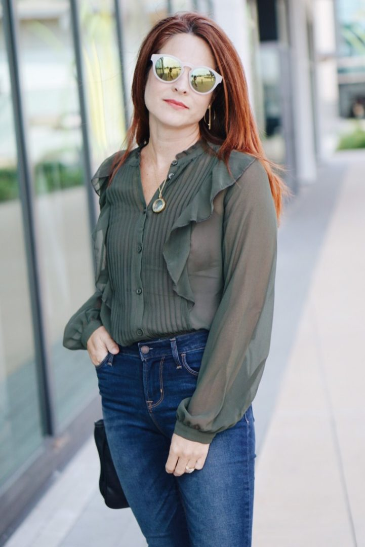 white sunglasses, sheer blouse, red hair, work attire, business casual, high-wasited skinny jeans