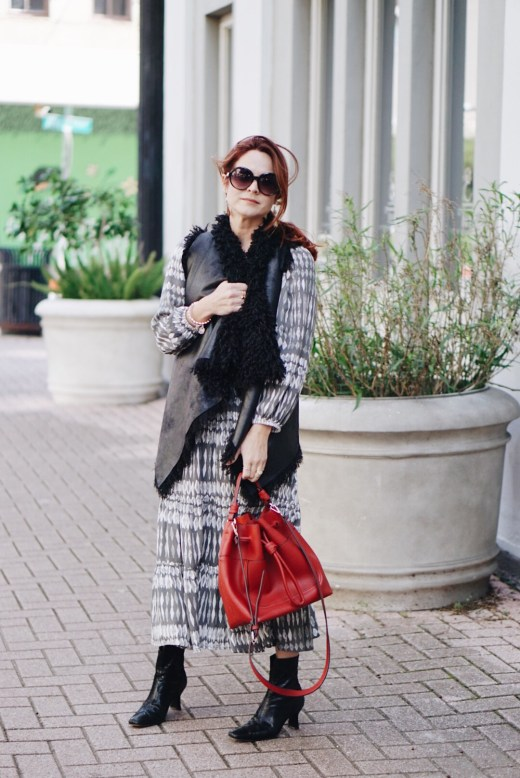 leather vest, shag vest, red bucket bag, styling a long vest with a dress, black boots, shag, round black sunglasses, mary kate and ashley olsen inspired outfit