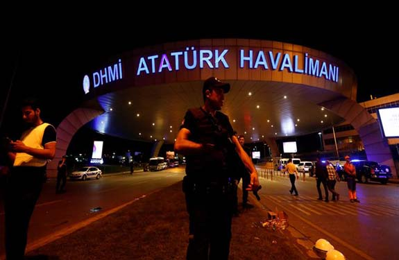 A riot police officer stands guard at the entrance of the Ataturk airport in Istanbul, Turkey, following a multiple suicide bombing