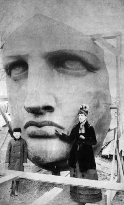 The woman who was the model for the face of the Statue of Liberty standing beside it.