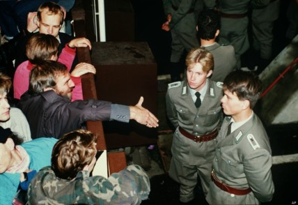 At the fall of the Berlin Wall. Bystanders reaching out to shake hands with East German border guards
