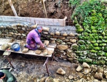 """A view of the wall construction from above. Most of these stones are the same stones from the fallen section. The """"new"""" section transitions nicely to the remaining section of the old wall. Now, we just need some moss to make it blend in."""