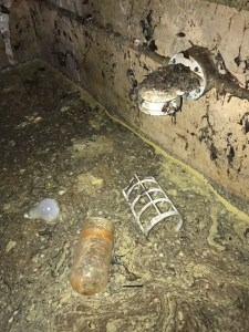 Debris floating on sludge build up inside of an elevator pit