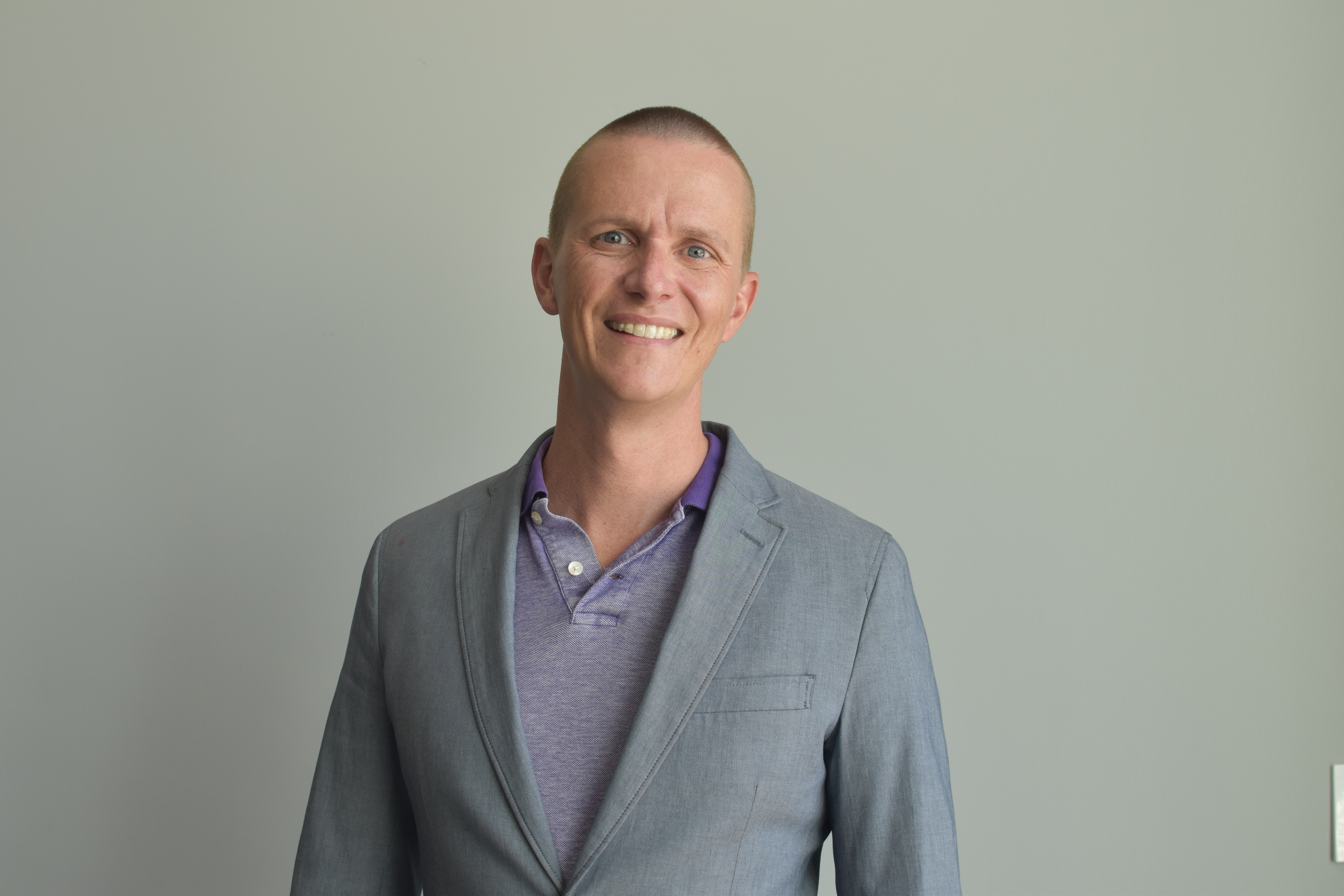 Tim Grivois-Shah is wearing a purple shirt with a collar and a grey sport coat. He is smiling. The background is grey.