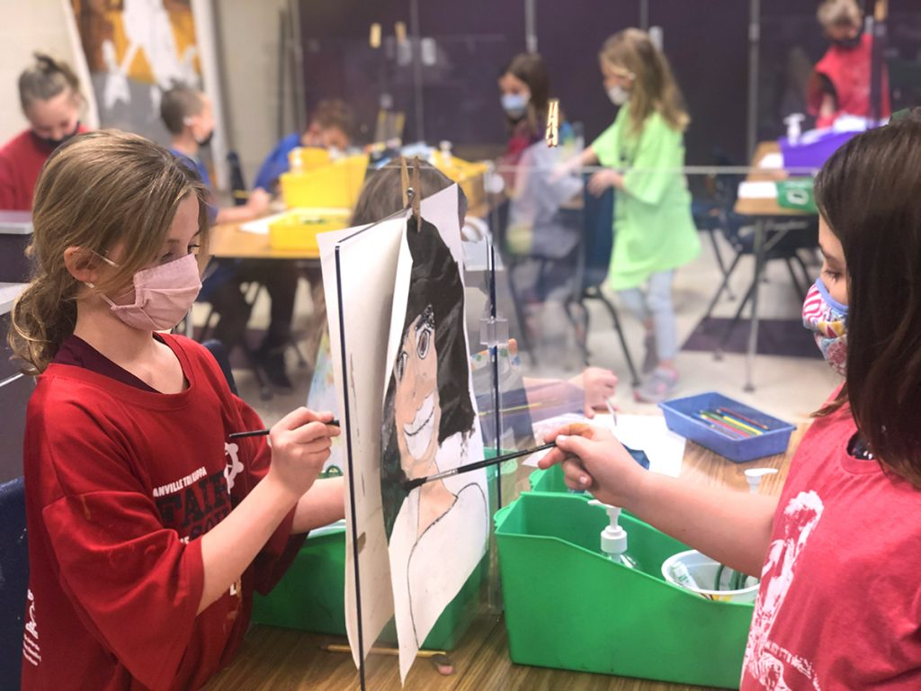 Students using plexiglass dividers as easels for drawing portraits