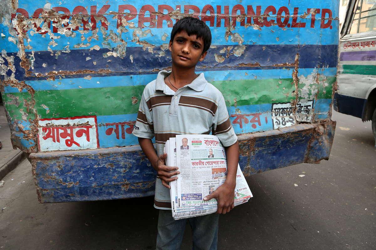 通りで新聞を売る少年