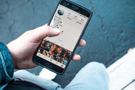 Foto de alguém segurando o celular, enquanto acessa o Instagram