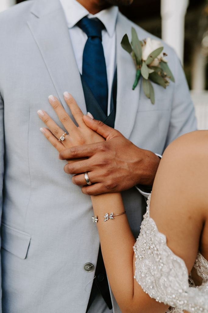 Closeup of Bride's hand on Groom's chest with wedding bands and engagement ring on