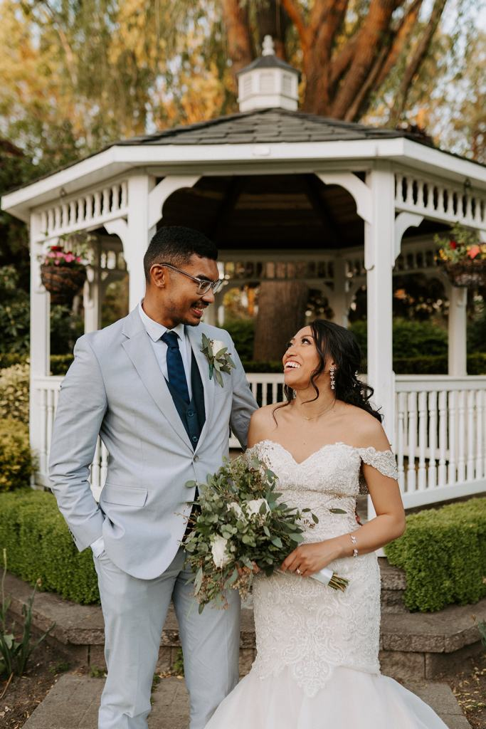 Bride and Groom looking at each other side by side in front of gazebo