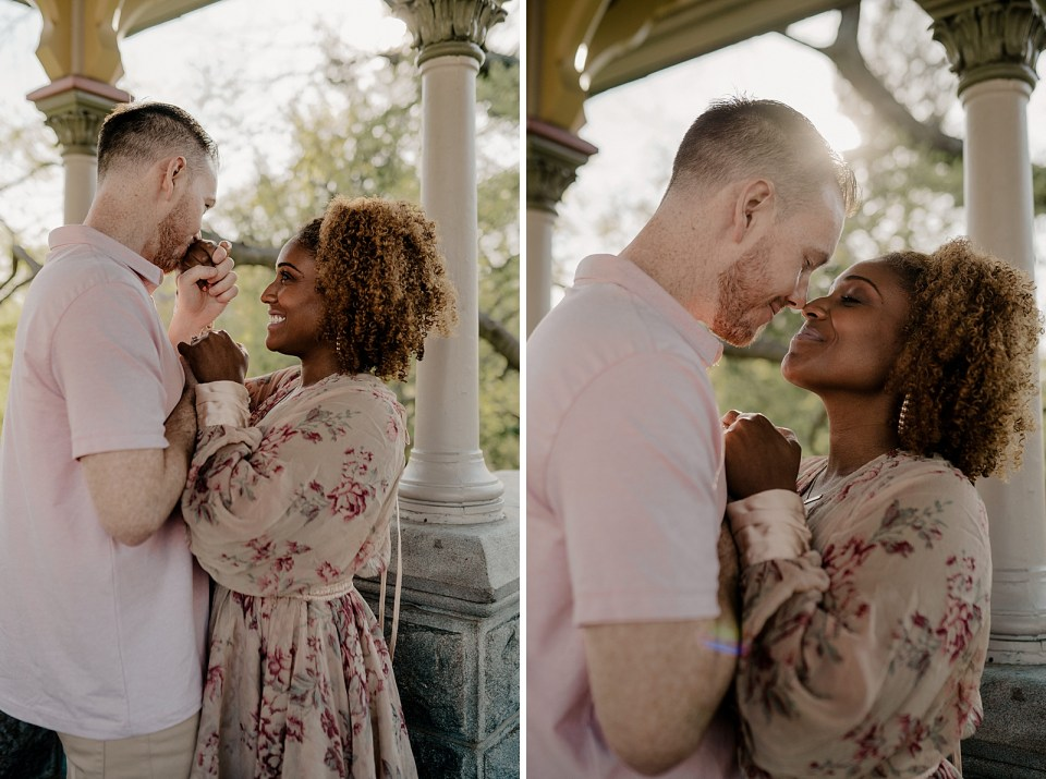Couple standing face to face and man holding and kissing woman's hand