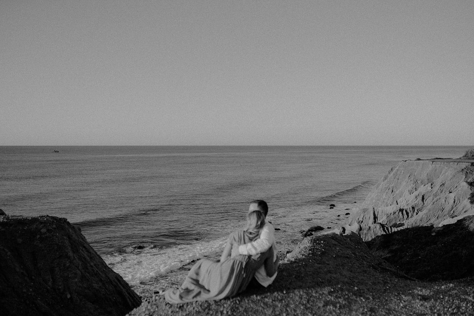 B&W Couple sitting on gravel sand in front of the ocean