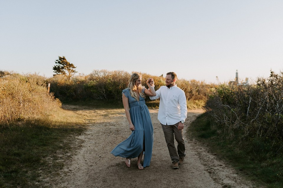 Couple holding hands up and walking on sand path together