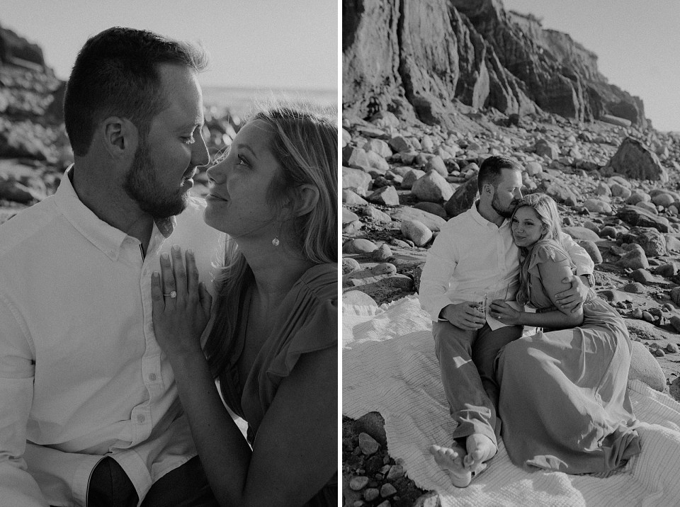 B&W Couple looking at each other sitting on rocky beach