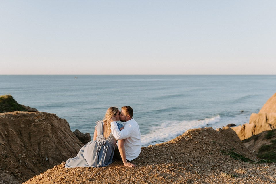 Couple sitting on gravel sand kissing in front of the ocean
