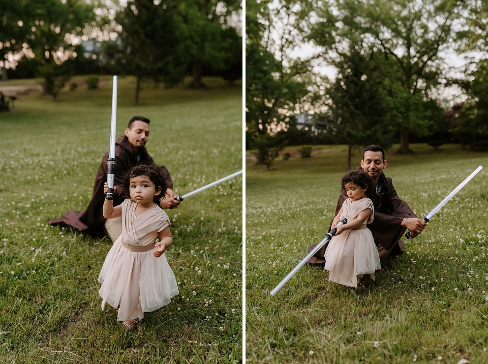 Dad crouching down with lightsaber in front of toddler with lightsaber on grass field