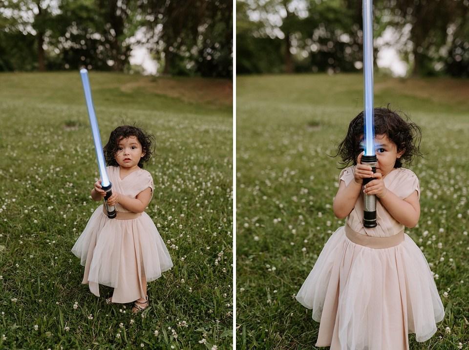 Toddler Daughter holding blue lightsaber on grassy field