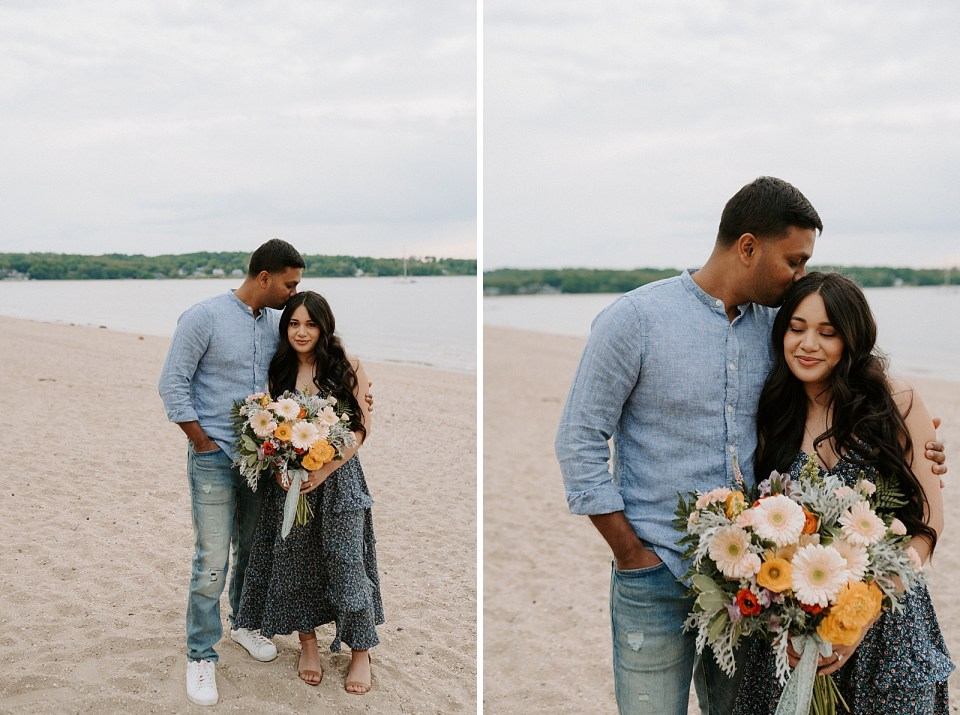 Man holding woman kissing woman's head with woman holding bright summer bouquet on the beach