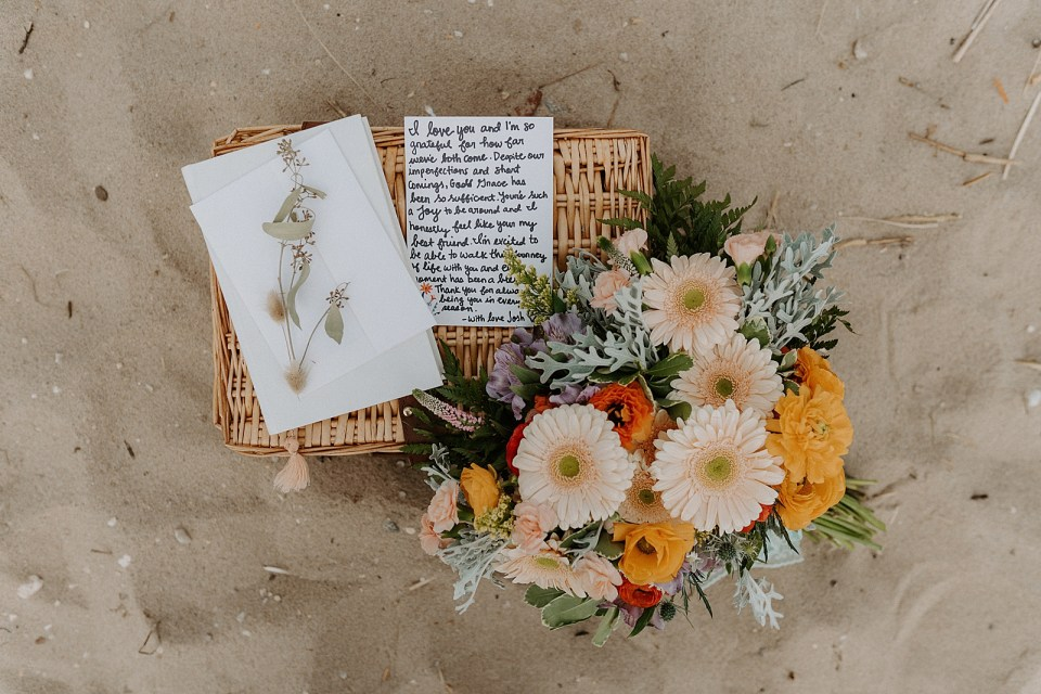 Detail shot of basket letter and bouquet on the sand