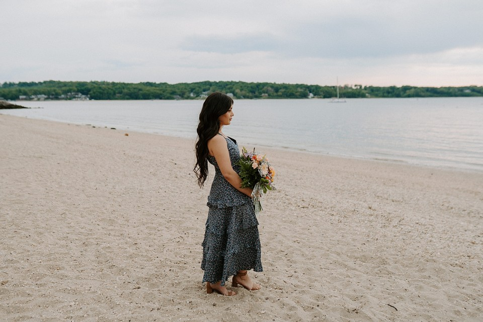 Portrait of woman holding bouquet on the beach