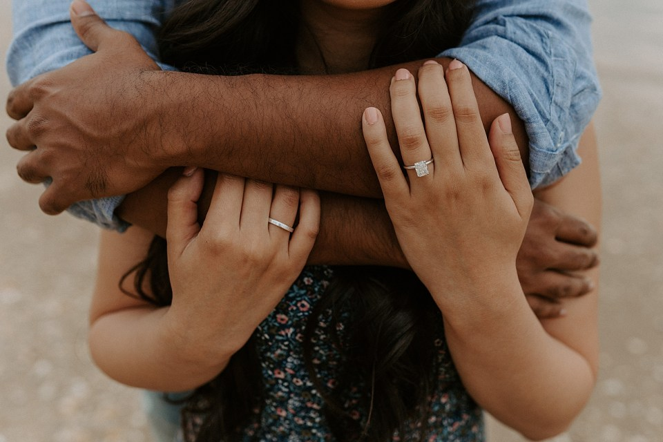 Closeup of man wrapping arms around woman and woman's hands with square diamond engagement ring