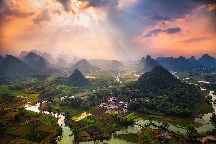 Light beams piercing the sky as seen from the top of Cuipingshan Hill in Yangshuo, China.