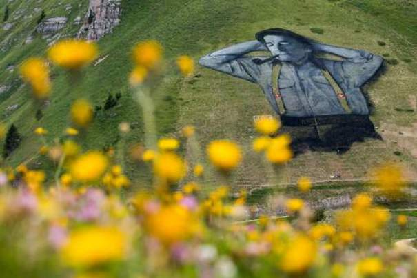 A fresco painted on grass with biodegradable paint, representing a Swiss shepherd on 10'000 square meters, by French artist Saype, is pictured Thursday, Aug. 4, 2016, in Leysin, Switzerland. (Jean-Christophe Bott/Keystone via AP)