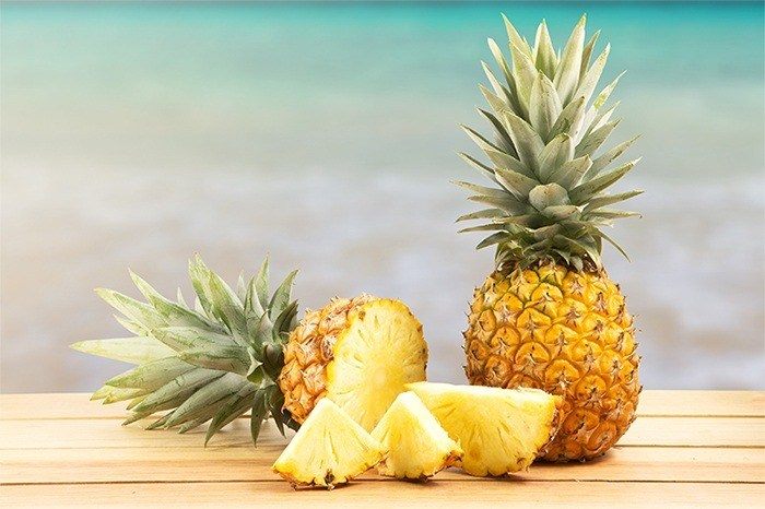 pineapple on wooden table in a tropical landscape