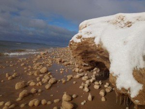 Took this picture along the Lake Michigan shoreline. Thousands of sandy ice balls form when rolls of light snow are blown form the shore into water which is at or just below freezing. The rolls of snow are then tossed about in the chilly waters and mix with sand in the churning water, where wave action eventually shapes them into balls of sandy ice!