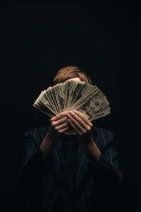 person-holds-money-in-front-of-face