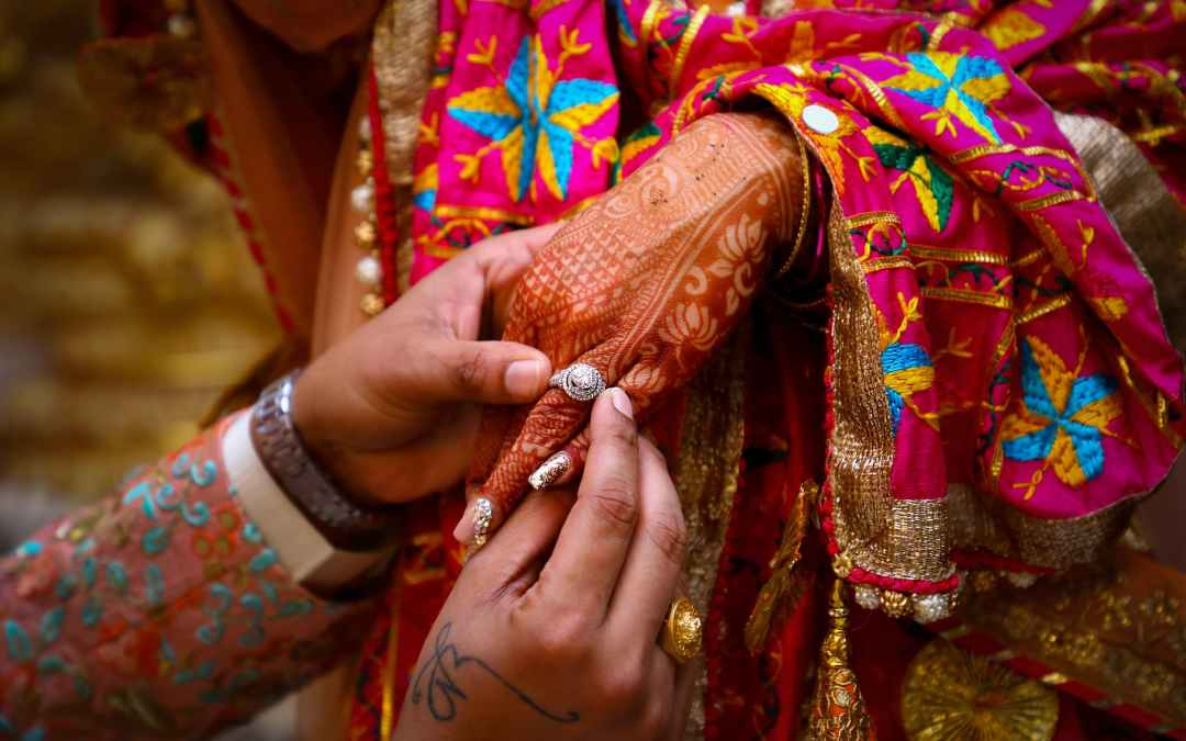 crop indian man giving ring to woman during traditional wedding ceremony