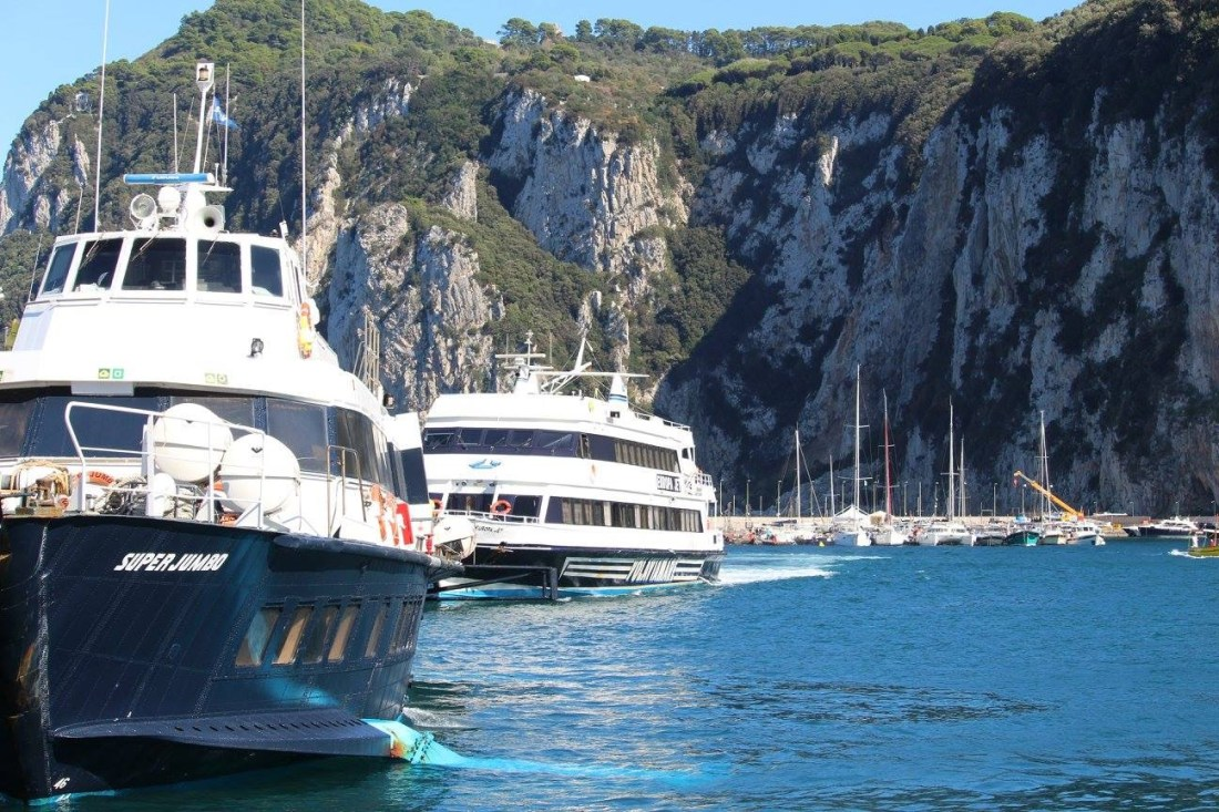 The ferry to Sorrento moored in Capri harbour, on blue seas