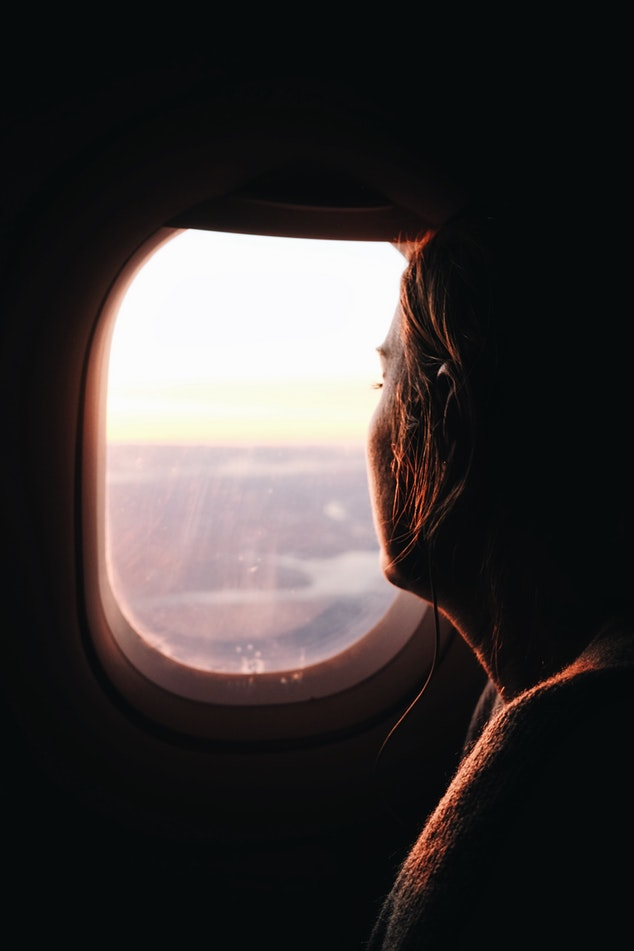 Woman traveling on flight looking out of window
