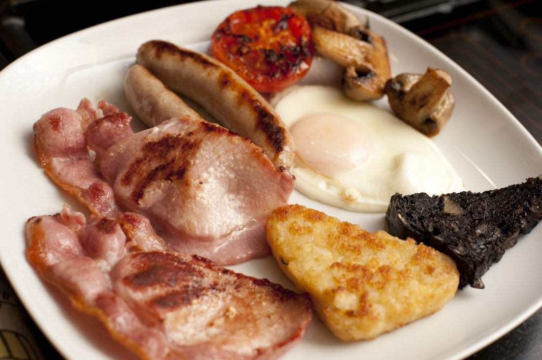 A full english breakfast with bacon, sausages, and black pudding - 23 Things You Should Know Before Visiting The UK